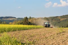 Blue tractor in a field of mustard in the Czech Republic. Dusty field and agricultural work. Autumn farm chores. Stock Photo