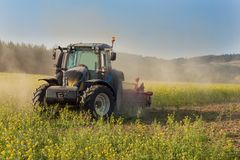 Blue tractor in a field of mustard in the Czech Republic. Dusty field and agricultural work. Autumn farm chores. Stock Photography