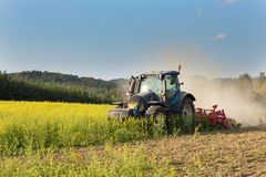 Blue tractor in a field of mustard in the Czech Republic. Dusty field and agricultural work. Autumn farm chores. Stock Images