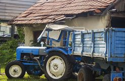 Blue tractor parking at the courtyard of the old, aged house. Re stock photo
