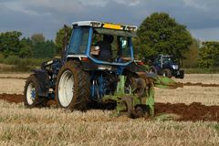 Blue tractor ploughing Stock Photo