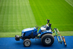Blue tractor with a plow near the football field with green grass. The concept of sport fields preparation and Stock Photo