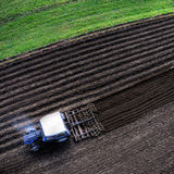 Blue tractor plowing, aerial top view. Aerial shot of blue tractor plowing the brown field during the autumn Stock Photos