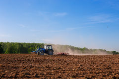 Blue tractor plowing field in spring. Blue tractor with bucket plowing field in spring stock photography
