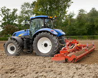 Blue Tractor Pulling Power Harrow Stock Images