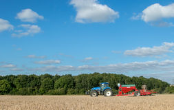 A blue tractor with a seed drill in a ploughed field Stock Photos