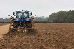 Blue tractor tilling Stock Images