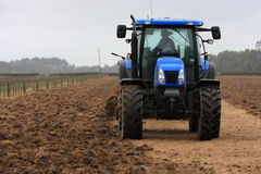 Blue tractor tilling Stock Image