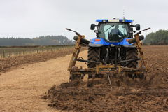 Blue tractor tilling Royalty Free Stock Photos