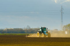 Blue tractor working on thre agricultural field Stock Photo