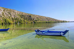 Blue traditional old wooden fishing boat with Greece flag Royalty Free Stock Photos