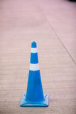 Blue traffic cone on street. Traffic cone with white and blue stripes on gray road stock photography