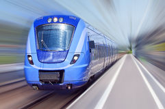 Blue train in motion. A passenger train travels at high speed through a train station with everything bar the train blurred out Stock Photo