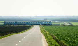 Blue train passing over road Stock Photos