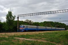 Blue train, railroad along trees line, horizontal composition, spring cloudy day. In Ukraine royalty free stock photos
