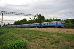 Blue train, railroad along trees line, horizontal composition, spring cloudy day. In Ukraine stock photography