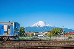 Blue train on railroad tracks with Mount Fuji. At Kawaguchiko , japan in summer stock photo