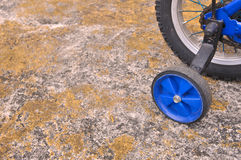 Blue training wheels on a children's bicycle Royalty Free Stock Photo