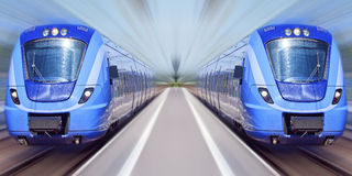 Blue trains in motion. Two passenger trains travel at high speed through a train station with everything bar the trains blurred out Stock Photo