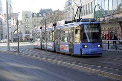 A blue tram in downtown Munich on a bright winter`s morning. A tram passesthrough Munich city centre in January as workers` unions threaten strikes across the Royalty Free Stock Images