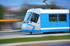 Blue tram rider fast on rails Royalty Free Stock Photography