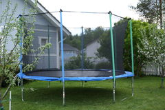 Blue trampoline on the lawn in garden Stock Image