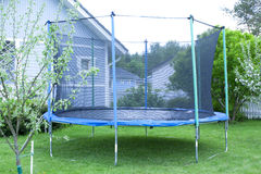 Blue trampoline on the lawn in garden Stock Photography
