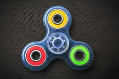 Blue transparent Fidget Spinner with colorful rings, stress relieving toy royalty free stock images