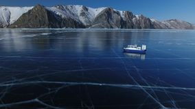 Blue Transparent Ice field Lake Baikal Picturesque cracks. Khivus ship boat an air cushion rides near high mountains. Best Russia