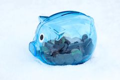 Blue transparent Piggy bank with Euro cent on the snow stock images