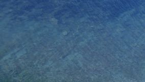 Blue transparent sea water with stone bottom and small rippled.