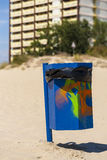 Blue trash basket with grafitti on the beach. Stock Photo