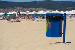 Blue trash basket with grafitti on the beach. Royalty Free Stock Image
