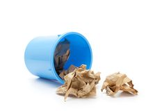 Blue trash can with crumpled paper spilling out Royalty Free Stock Images