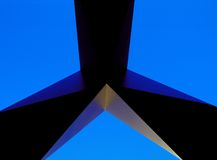 Blue Triangle. An abstract view of a sculpture showing three blade like fingers forming a triangle with a blue sky Royalty Free Stock Photos