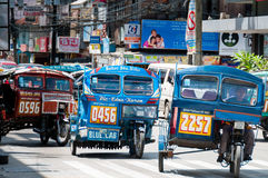 Blue Tricycles of Dumaguete driving on The Road Stock Images