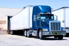 Blue Truck At Dock. This is a picture of 18 wheeler semi truck loading at a warehouse building