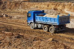 Blue truck and going through gravel ground. Works of digging Royalty Free Stock Images