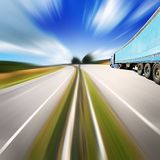Blue truck on Highway throurg the summer fields Stock Image