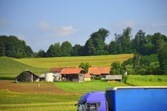 Blue truck in beautiful scenery along A2 motorway Slovenia Europe. Blue truck moving in a nice area along Zaloke village traditional houses,Zaloke is a royalty free stock images