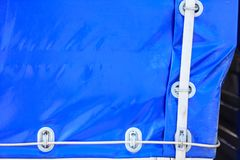 Blue truck tarpaulin close up. Detailed close up of blue tarpaulin with wires and ropes. Truck details concept Royalty Free Stock Images
