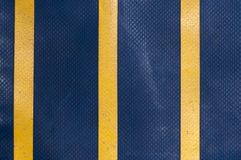 Blue truck tarpaulin with yellow stripes. Abstract background of a blue truck tarpaulin with yellow stripes Stock Photography