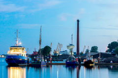 Blue tug ship moored at the pier. Of Riga. Evening landscape with stock image