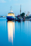 Blue tug ship moored at the pier. Of Riga. Evening landscape with stock photos