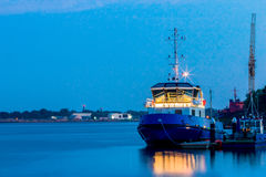 Blue tug ship moored at the pier. Of Riga. Evening landscape with Royalty Free Stock Images