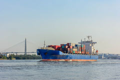 Blue tugboat sailing in calm seas. Commercial cargo ship carrying containers arriving port Royalty Free Stock Photo