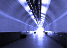Blue tunnel. Blue pedestrian tunnel with light at the end Royalty Free Stock Images