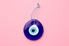 Blue turkish eye. On pink background stock photo