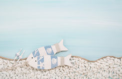 Blue or turquoise background with two wooden fishes and shells f Royalty Free Stock Photos