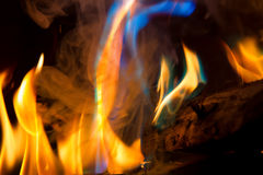 Blue Turquoise Flame. Close up of blue, orange, and turquoise flames in a fireplace. Lots of smoke and a log. Long exposure to make the flames look soft Royalty Free Stock Photos